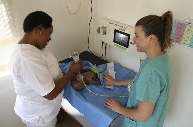 Jordmor Fortunata og Monica trener maske-bag-ventilasjon med Upright-bag på Haydom sykehus i Tanzania. Utstyret i bakgrunnen brukes til monitorering og datainnsamling, kan vise hjertefrekvensen basert på tørr-elektrode-EKG og måler trykk, flow og endetidal CO2 (sidestream).